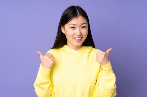 Jeune, femme asiatique, sur, mur pourpre, à, pouces haut, geste, et, sourire