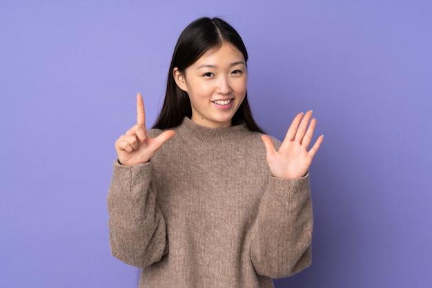 Jeune femme asiatique sur mur violet comptant sept avec les doigts