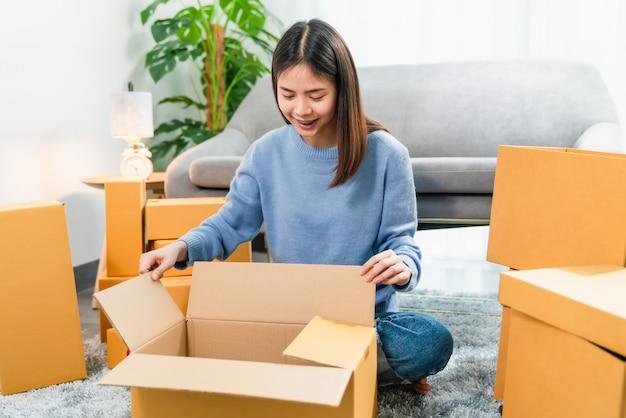 Jeune femme asiatique ouvrant une boîte alors qu'il était assis sur le sol