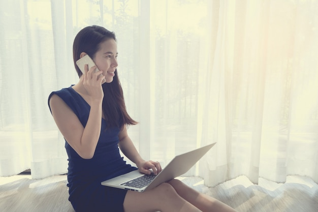 Jeune femme asiatique parle de téléphone et à l'aide d'un ordinateur portable.