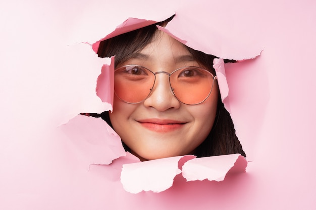 Une jeune femme asiatique passa la tête à travers le papier déchiré