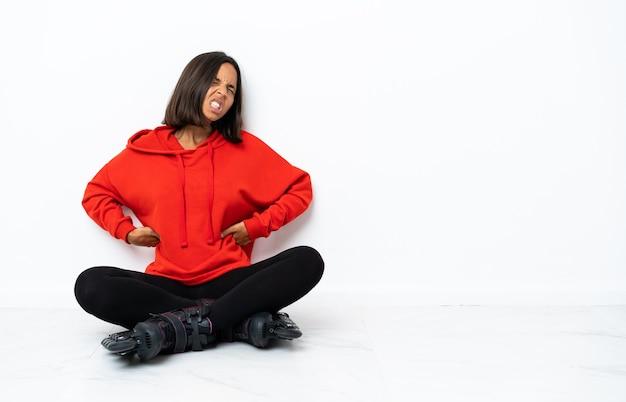 Jeune femme asiatique avec des patins à roulettes sur le sol souffrant de maux de dos