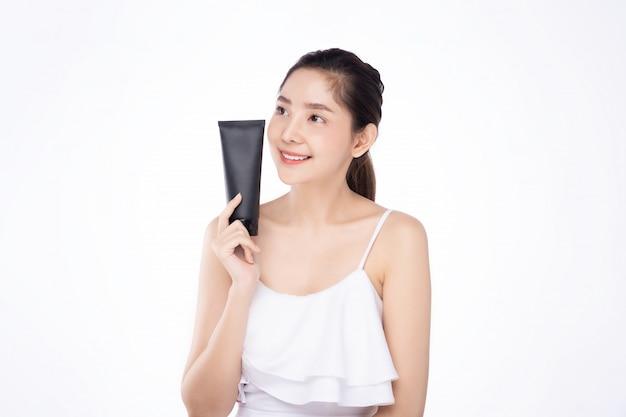 Jeune femme asiatique avec une peau blanche fraîche et propre tenant une crème de soin du visage