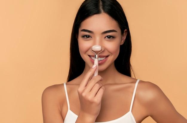 Une jeune femme asiatique à la peau propre et radieuse fait un massage du visage avec un rouleau de quartz sur un mur beige.