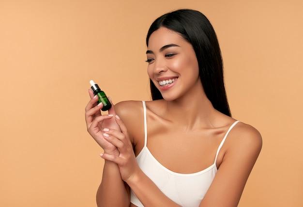 Une jeune femme asiatique à la peau propre et radieuse en lingerie blanche tient un sérum hydratant sur beige