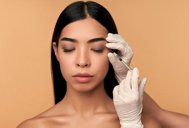 Une jeune femme asiatique à la peau propre et radieuse reçoit des injections de botox pour resserrer les contours, augmentation des lèvres sur beige