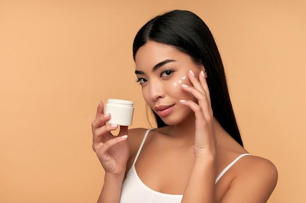 Une jeune femme asiatique à la peau propre et radieuse utilise une crème hydratante pour le visage sur beige