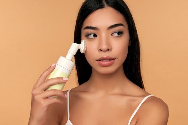 Une jeune femme asiatique à la peau radieuse nettoie son visage avec une brosse et une mousse isolée sur beige
