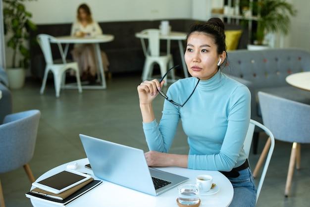 Jeune femme asiatique pensive en tenue décontractée assis par table devant un ordinateur portable au café et l'analyse des données