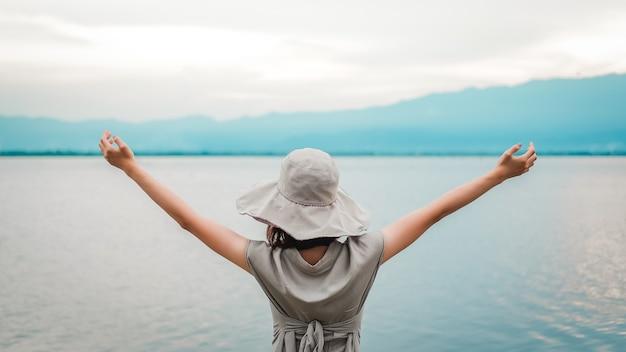 Jeune femme asiatique portant un chapeau et levant les bras tendus avec des lacs et des montagnes. bonheur et profiter. vue arrière de la nature touristique et magnifique.