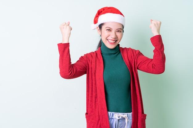 Jeune femme asiatique portant un chapeau de noël sur fond vert, concept de noël