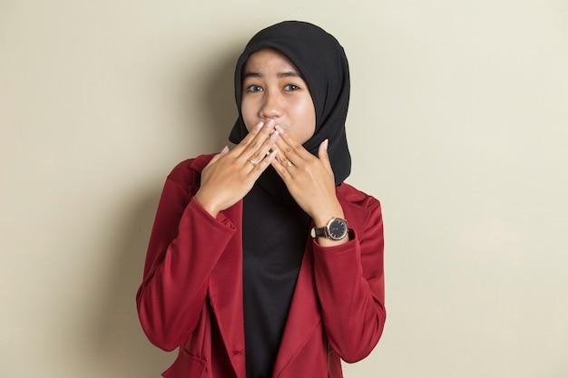 Jeune femme asiatique portant le hijab choqué couvrant la bouche avec les mains par erreur. concept secret.