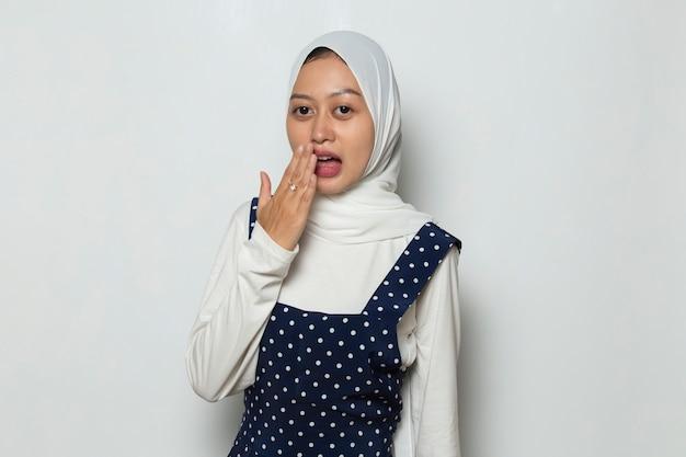 Jeune femme asiatique portant le hijab choquée couvrant la bouche avec les mains pour erreur concept secret