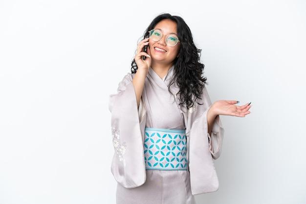 Jeune femme asiatique portant un kimono isolé sur fond blanc en gardant une conversation avec le téléphone portable avec quelqu'un