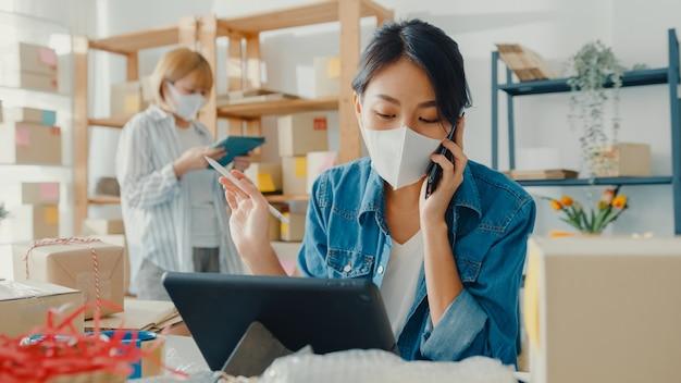 Jeune femme asiatique portant un masque facial à l'aide de téléphone mobile recevant un bon de commande et vérifiant le produit sur le travail en stock au bureau à domicile