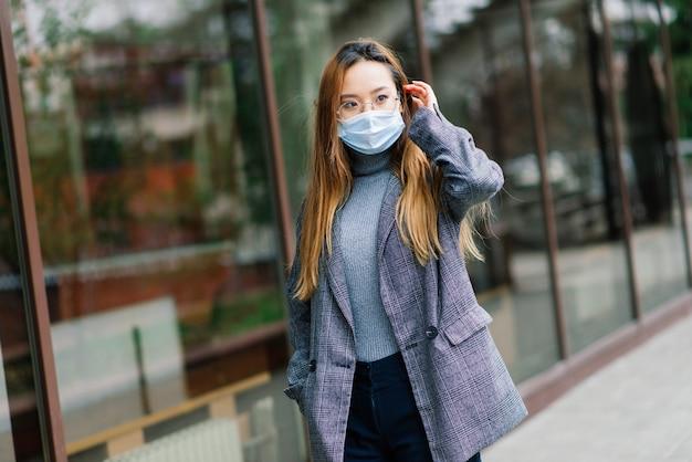 Jeune femme asiatique portant un masque facial est debout dans une rue domestique. nouvelle épidémie normale de covid-19