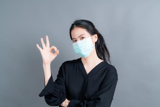 Jeune femme asiatique portant un masque médical protège la poussière de filtre pm2.5 anti-pollution, anti-smog, covid-19 et montrant le signe ok