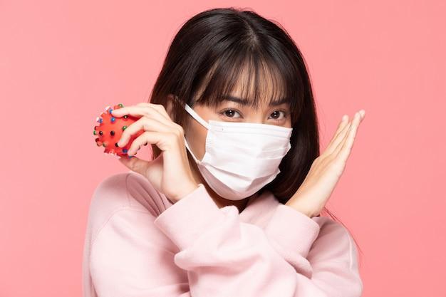 Jeune femme asiatique portant un masque de protection ou un masque chirurgical pour protéger contre les virus et la pollution de l'air faisant croix arrêter la main et tenir le virus sur place sur le mur rose, soins de santé et concept de coronavirus