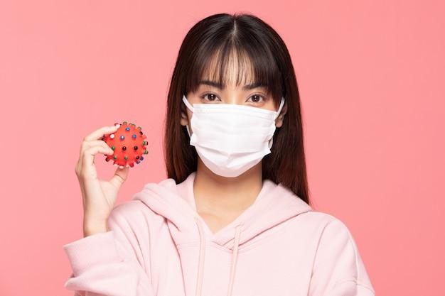 Jeune femme asiatique portant un masque de protection ou un masque chirurgical pour les virus protégés et la pollution de l'air faisant arrêter la main et tenir le virus sur place sur le mur rose, concept de soins de santé et de coronavirus