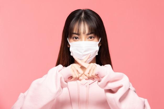 Jeune femme asiatique portant un masque de protection ou un masque chirurgical pour les virus protégés et la pollution de l'air faisant le virus d'arrêt de la main croisée sur le mur rose, concept de soins de santé et de coronavirus