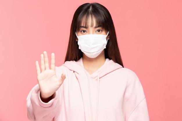 Jeune femme asiatique portant un masque de protection ou un masque chirurgical pour les virus protégés et la pollution de l'air, rendant le virus d'arrêt sur le mur rose, les soins de santé et le concept de coronavirus