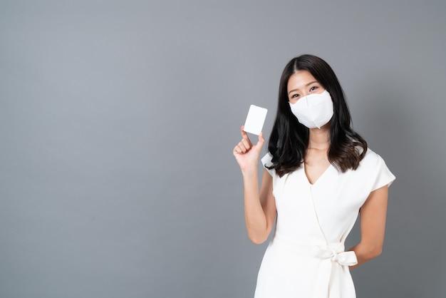 Jeune femme asiatique portant un masque et utilisant un spray d'alcool à portée de main pour protéger le virus corona (covid-19)