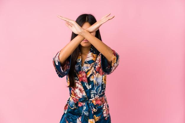 Jeune femme asiatique portant un pyjama kimono en gardant deux bras croisés, concept de déni.