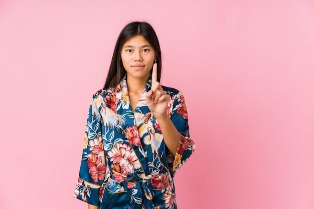 Jeune femme asiatique portant un pyjama kimono montrant le numéro un avec le doigt.