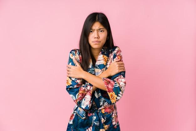 Jeune femme asiatique portant un pyjama kimono qui devient froid en raison d'une basse température ou d'une maladie.