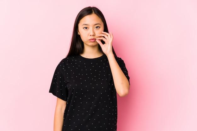 Jeune femme asiatique portant des vêtements élégants isolés avec les doigts sur les lèvres gardant un secret.