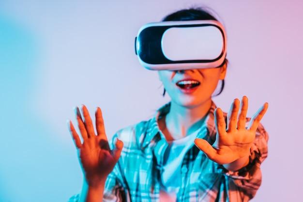 Une jeune femme asiatique porte des lunettes vr pour découvrir la technologie de réalité augmentée