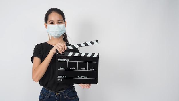 Une jeune femme asiatique porte un masque facial et une main tenant un panneau de clapet ou une ardoise de film dans la production vidéo, le cinéma, l'industrie du cinéma sur fond blanc.