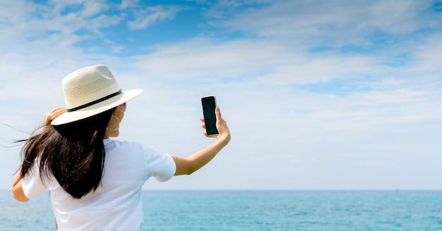 Jeune femme asiatique porter un chapeau dans un style décontracté, utiliser un smartphone prenant selfie au quai. vacances d'été sur la plage paradisiaque tropicale. voyage fille heureuse en vacances. vibes d'été.