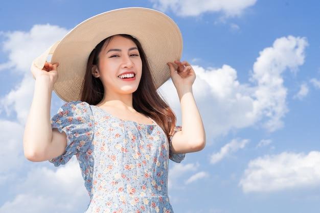 Jeune femme asiatique posant sur fond de ciel