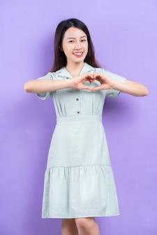 Jeune femme asiatique posant sur fond violet