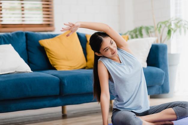 Jeune femme asiatique pratiquant le yoga dans le salon.