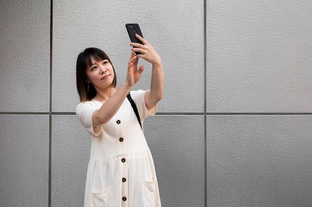 Jeune femme asiatique prenant un selfie