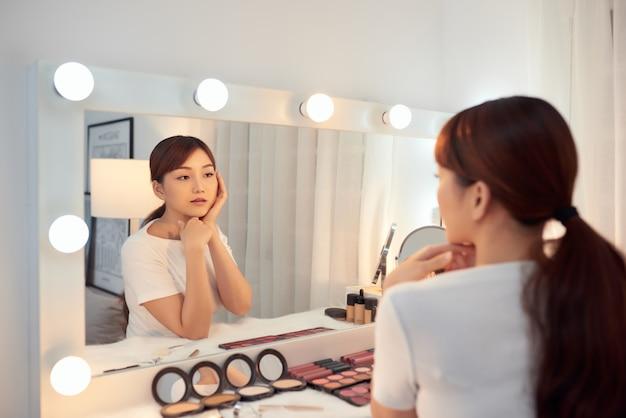 Jeune femme asiatique prenant soin de sa peau tout en regardant dans le morror