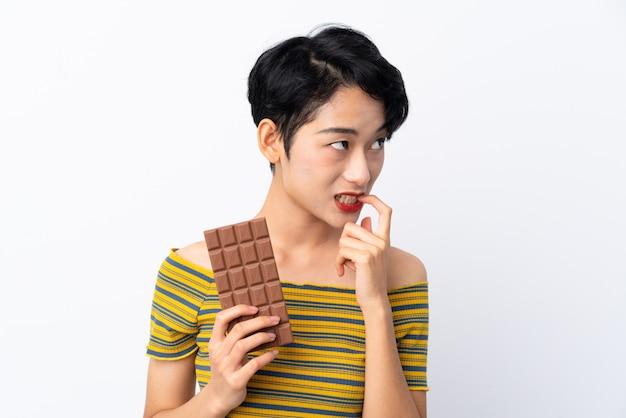 Jeune femme asiatique prenant une tablette de chocolat et ayant des doutes