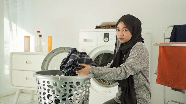 Jeune femme asiatique prenant des vêtements sales pour se laver avec un visage sombre à la maison