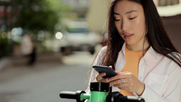 Jeune femme asiatique prendre un scooter électrique partageant un parking application téléphonique touristique femme utilisant une application téléphonique pour louer un scooter électrique