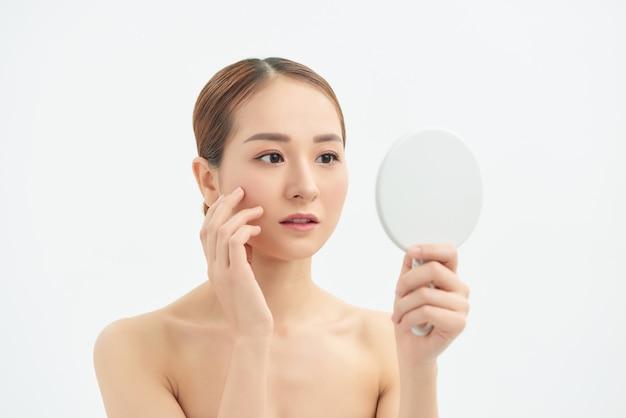Jeune femme asiatique avec un problème de visage regardant le miroir sur fond blanc.