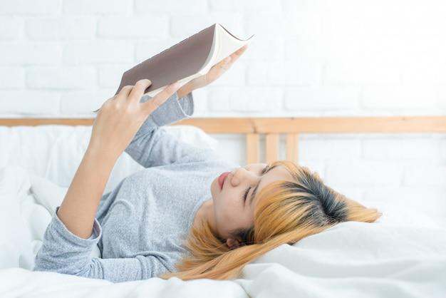 Jeune femme asiatique profitant de s'allonger sur le lit en lisant un livre plaisir en vêtements décontractés à la maison