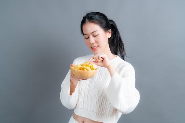 Jeune femme asiatique en pull blanc manger des croustilles sur mur gris