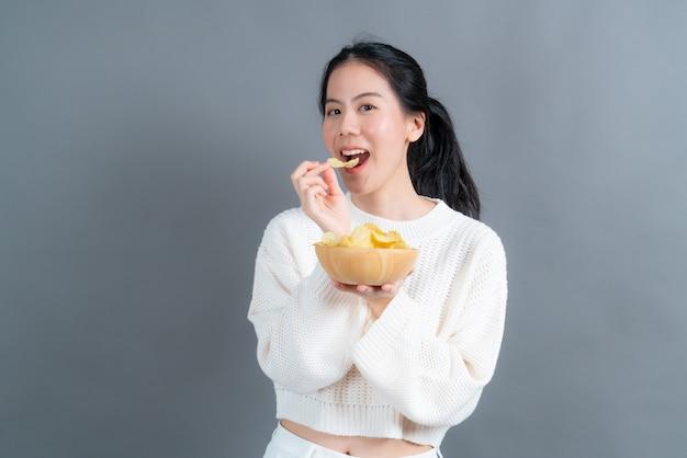 Jeune femme asiatique en pull blanc manger des croustilles