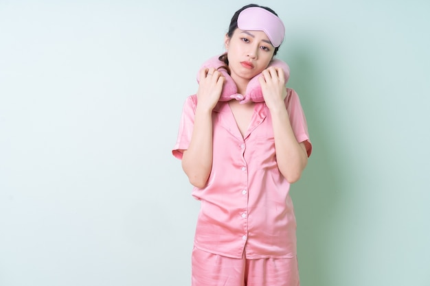 Jeune femme asiatique en pyjama sur fond vert