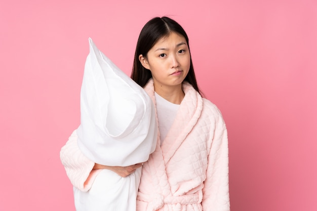 Jeune femme asiatique en pyjama isolé sur rose avec une expression triste