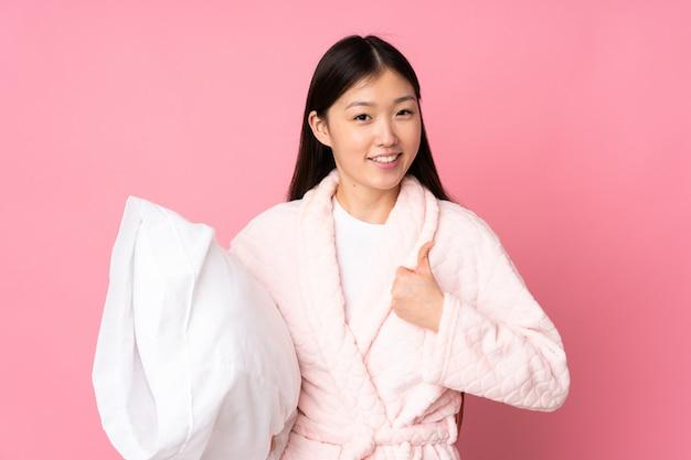 Jeune femme asiatique en pyjama sur mur rose avec les pouces vers le haut parce que quelque chose de bien s'est produit