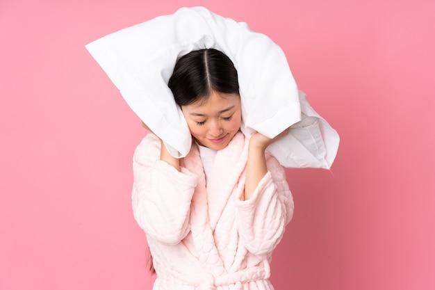 Jeune femme asiatique en pyjama sur mur rose