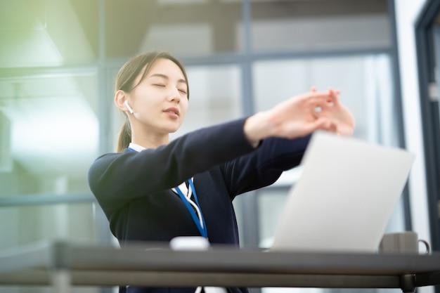 Jeune femme asiatique qui s'étend au travail